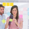 Colleagues pasting sticky note — Stock Photo #25726651