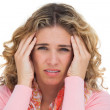 Blonde woman suffering with headache thus touching her temples — Stock Photo