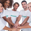 Smiling volunteer group putting hands together — Stock Photo