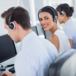 Attractive call centre employee looking over shoulder — Stock Photo #25726987