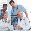 Stock Photo: Smiling medical team examining radiography