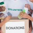 Volunteers putting food in donation box — Stock Photo #25727129