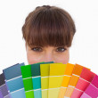 Stockfoto: Happy womwith fringe showing colour charts close up