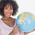 Happy woman pointing to globe — Stock Photo #25727339