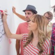 Creative team watching coworker add to flowchart — Stock Photo