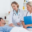 Foto Stock: Doctors talking to patient