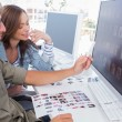Photo editor pointing at thumbnail on screen with colleague — Stock Photo
