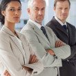 Three serious business standing together — Stock Photo