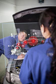Smiling mechanic looking up at colleague with a futuristic inter — Stock Photo