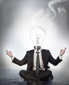 Businessman with bulb head sitting in meditation position — Stock Photo