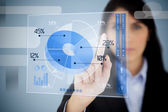 Serious businesswoman using blue pie chart interface — Foto Stock