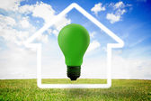 Green light bulb with white house outline — Stock Photo
