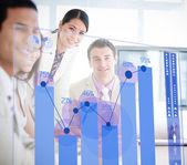 Uśmiechający się pracownicy firmy patrząc na interfejs niebieski wykres — Zdjęcie stockowe