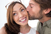 Man giving pretty woman kiss on the cheek — Stock Photo