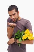Handsome man blowing a kiss and holding roses — Stock Photo