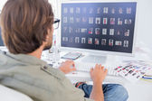 Photo editor viewing thumbnails on computer — Stock Photo