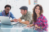 Creative team working together with one smiling at camera — Stock Photo