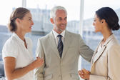 Likeable businessman speaking with female colleagues — Stock Photo