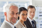 Smiling business looking in the same way — Stock Photo