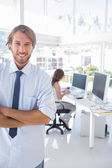 Smiling desginer standing in office with arms crossed — Stock Photo