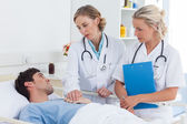 Two women doctors talking to a patient — Stock Photo