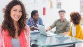 Smiling woman with creative team working behind — Stock Photo