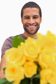 Handsome man offering bunch of yellow roses — Stock Photo