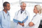 Three doctors examining a file — Stock Photo