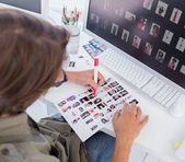 Over head of editor marking contact sheet — Stock Photo