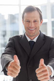 Smiling confident businessman giving thumbs up — Stock Photo