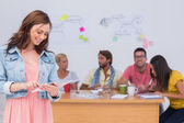 Woman using tablet with creative team working behind her — Stock Photo