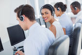 Smiling call centre employee looking over shoulder — Stock Photo