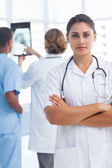 Serious woman doctor with arms crossed looking at the camera — Stockfoto