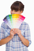 Pretty woman with fringe showing colour charts — Stockfoto