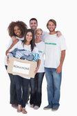 Happy group of volunteers holding donation box — Stock Photo