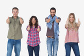 Fashionable friends looking at camera and giving thumbs up — Stock Photo