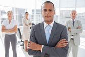 Serious businessman standing with arms crossed — Stock Photo