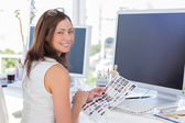 Editor looking over shoulder at camera at her desk — Stock Photo