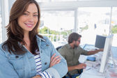Woman smiling in creative office with arms folded — Stock Photo