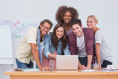 Creative team standing at desk with laptop — Stock Photo