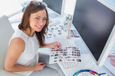 Smiling designer holding contact sheet — Stock Photo