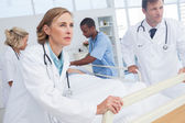 Doctors about to walk with patient bed — Stock Photo