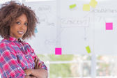 Happy woman with arms crossed in front of whiteboard — Stock Photo