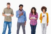Amigos de moda de pie en una fila mediante dispositivos de medios — Foto de Stock