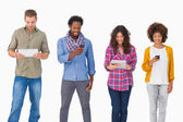 Fashionable friends standing in a row using media devices — Foto de Stock