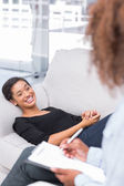Woman laughing on sofa during therapy session — Stock Photo