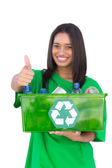 Enivromental activist holding box of recyclables and giving thumbs up — Stock Photo
