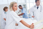 Serious doctors about to walk with patient bed — Stock Photo