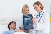 Two women doctors showing x-ray to a patient — Stock Photo