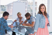 Team having meeting with one woman standing and smiling at camera — Stock Photo
